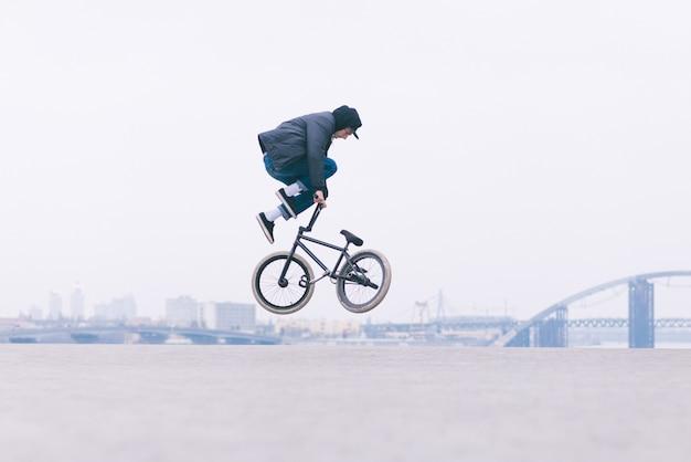 El joven lector de bicicletas bmx hace trucos en el aire sobre el paisaje urbano.