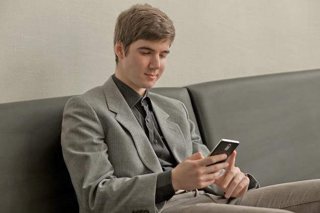 Joven lee noticias y mira videos en teléfonos inteligentes. el tipo sostiene el teléfono con las manos y desliza el dedo por la pantalla.