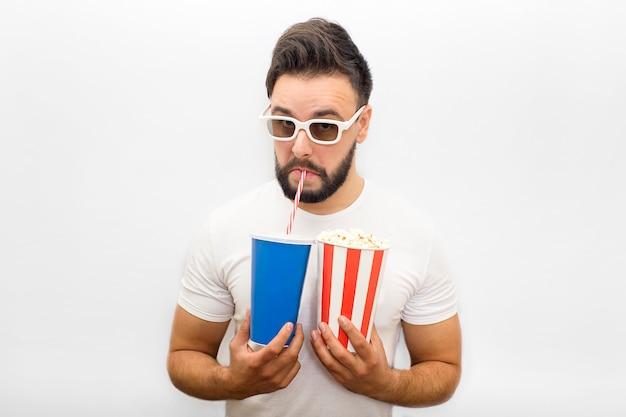 Joven se levanta y mira hacia abajo. lleva gafas de cine. guy sostiene un vaso de papel con palomitas de maíz y cola. bebe a través de la paja y mira.