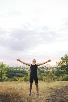 Joven levantando las manos sobre el cielo del atardecer después del entrenamiento