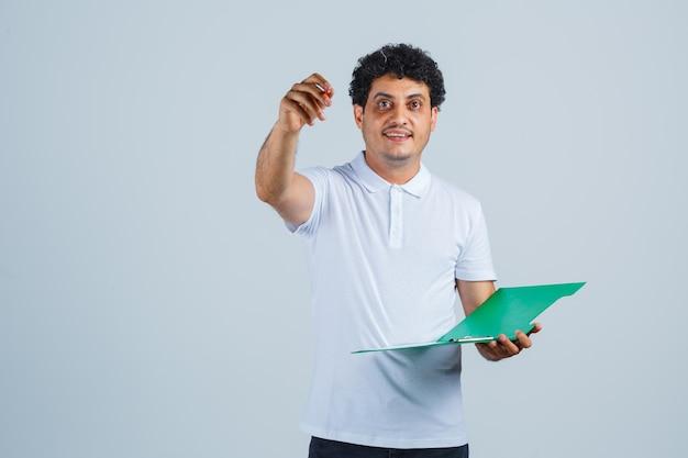 Joven levantando la pluma en gesto eureka y sosteniendo el cuaderno con camiseta blanca y jeans y luciendo sensato. vista frontal.