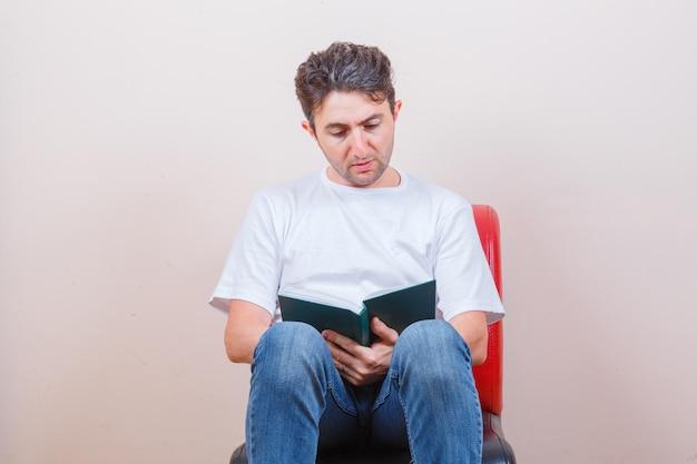 Joven leyendo el libro mientras está sentado en una silla en camiseta, jeans