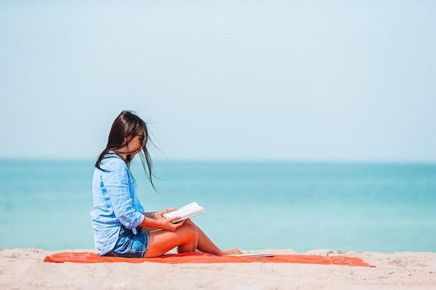 Joven leyendo el libro durante la playa blanca tropical
