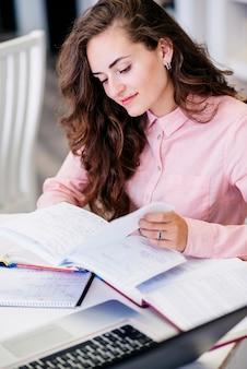 Joven leyendo notas en la mesa con la computadora portátil