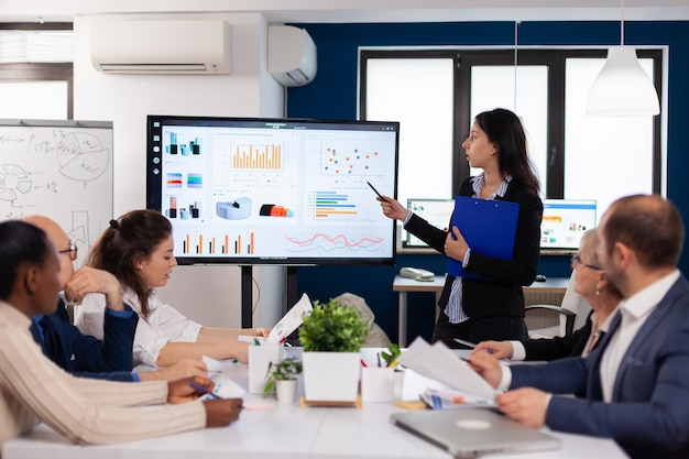 Joven líder de equipo en la gran corporación informando a los compañeros de trabajo apuntando al gráfico de la reunión del personal corporativo