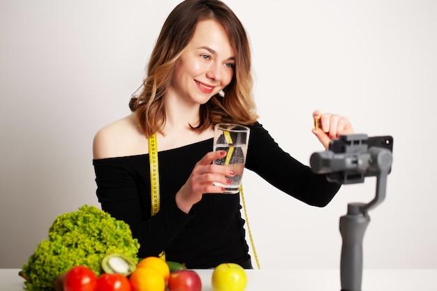 Una joven en lightroom escribe un blog sobre pérdida de peso y alimentación saludable.