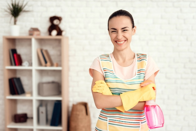 Joven limpia la casa con detergentes.