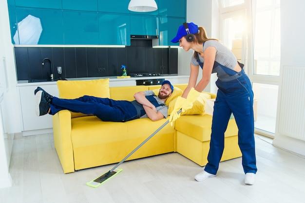 Joven limpiadora profesional en uniforme especial lavando el piso con un trapeador en el apartamento y su compañero de trabajo masculino acostado en el sofá y descansar en ese momento.