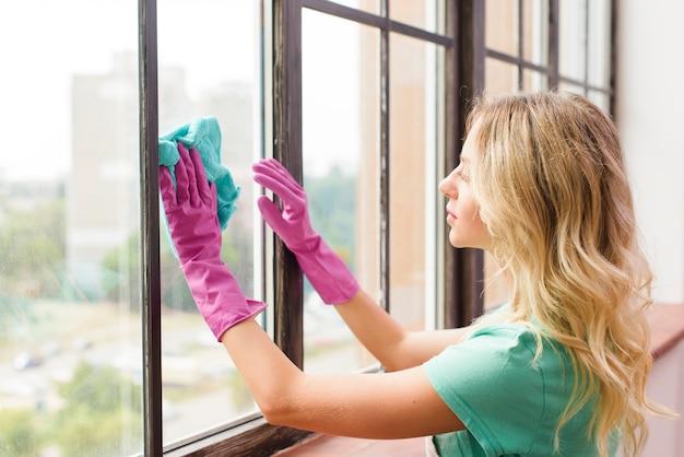 Joven, limpieza de ventanas con tela en casa