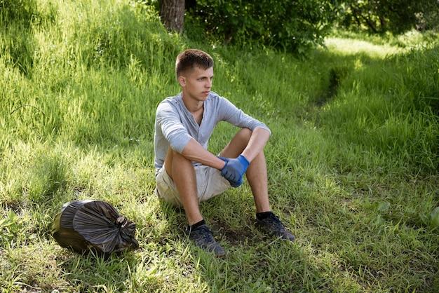 Un joven limpió voluntariamente el parque de basura se sienta en el césped con guantes descansando después del trabajo