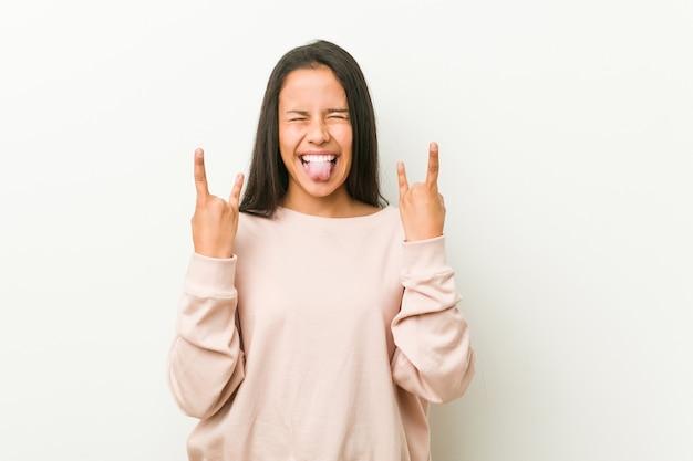 Joven linda adolescente hispana mostrando gesto de rock con los dedos