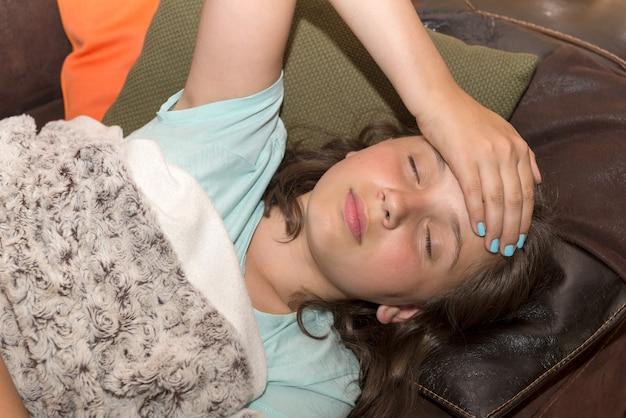 Joven linda chica caucásica tiene dolor de cabeza