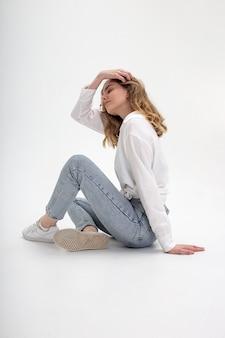 Joven linda chica pensativa caucásica posando en camisa blanca