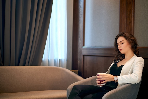 Joven linda chica pensativa tomando café en un café