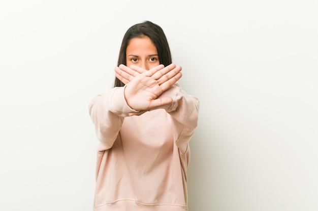 Joven linda mujer adolescente hispana haciendo un gesto de negación