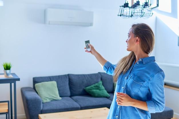 Joven linda mujer casual con aire acondicionado y ajuste de temperatura confortable con control remoto en el apartamento