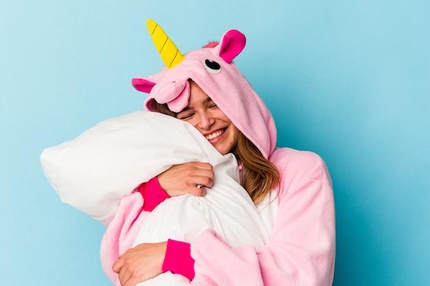Joven linda mujer caucásica vistiendo un pijama de unicornio sosteniendo una almohada aislada en azul