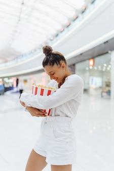 Joven linda mujer sosteniendo palomitas de maíz en el fondo del centro comercial