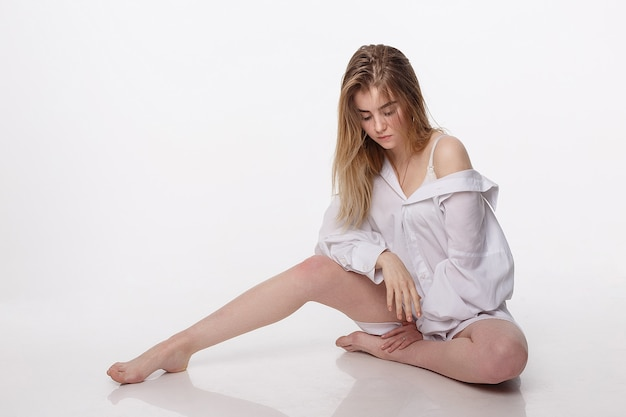 Joven linda mujer vistiendo camisa sentada en el piso con hombros y piernas desnudos