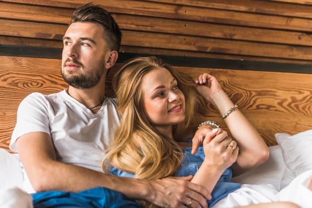 Joven linda pareja en la cama en casa