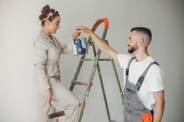 La joven y linda pareja repara la habitación