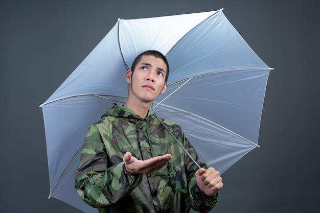 El joven lleva un impermeable de camuflaje y muestra diferentes gestos.