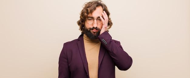 Joven loco con barba que se siente aburrido, frustrado y somnoliento después de una tarea aburrida, aburrida y tediosa, sosteniendo la cara con la mano contra la pared de color plano