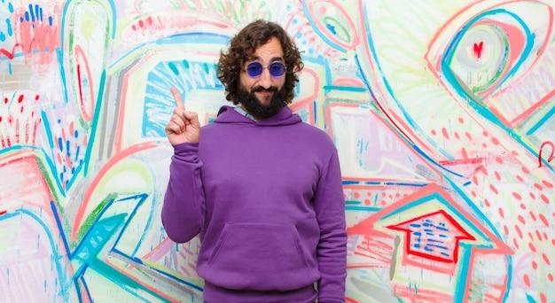 Un joven loco con barba que se siente como un genio con el dedo orgulloso en el aire después de darse cuenta de una gran idea, diciendo eureka contra el graffiti