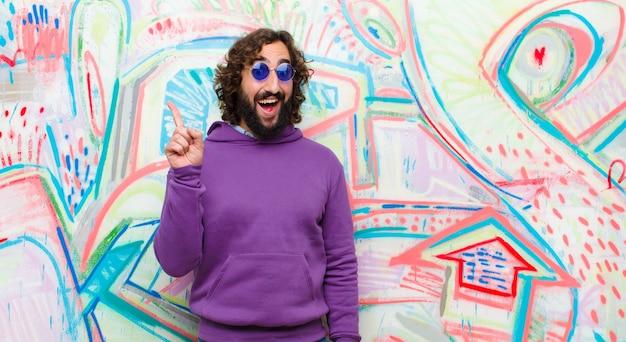 Joven loco con barba que se siente como un genio feliz y emocionado después de darse cuenta de una idea, levantando alegremente el dedo, ¡eureka! en la pared de graffiti