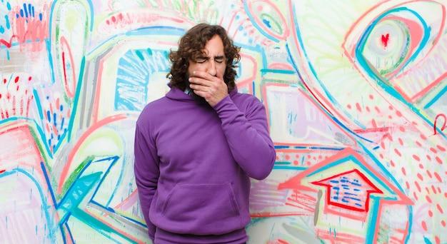 Joven loco con barba que se siente enfermo con dolor de garganta y síntomas de gripe, tos con la boca cubierta contra la pared de graffiti