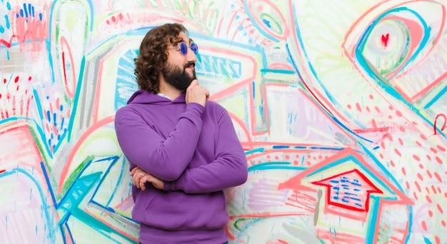 Un joven loco con barba se siente pensativo, se pregunta o imagina ideas, sueña despierto y mira hacia arriba para copiar el espacio contra la pared de graffiti