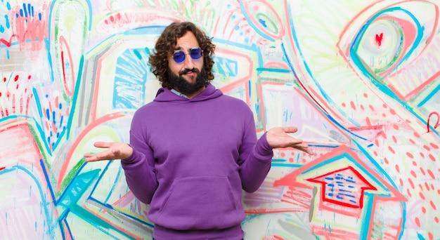 Un joven loco con barba se siente perplejo y confundido, inseguro sobre la respuesta o decisión correcta, tratando de tomar una decisión contra el graffiti