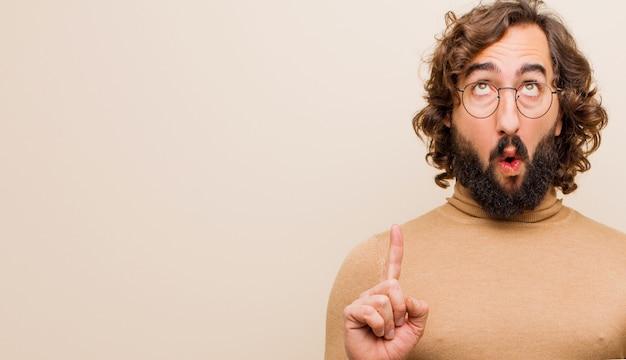 Joven loco barbudo que parece sorprendido, asombrado y con la boca abierta, apuntando hacia arriba con ambas manos para copiar el espacio contra la pared de color plano