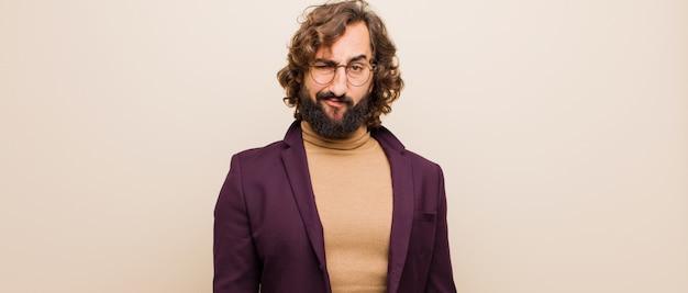 Joven loco barbudo que se siente confundido y dudoso, preguntándose o tratando de elegir o tomar una decisión contra la pared de color plano