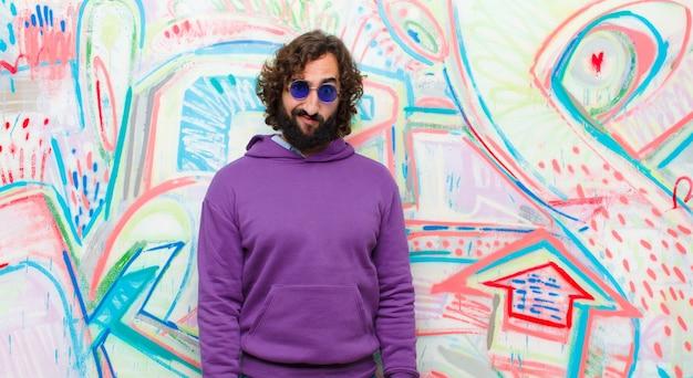 Joven loco barbudo que se siente confundido y dudoso, preguntándose o tratando de elegir o tomar una decisión sobre la pared de graffiti