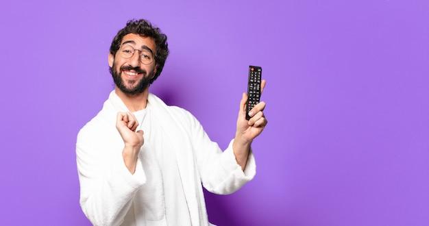 Joven loco barbudo vestido con albornoz con un mando a distancia de televisión
