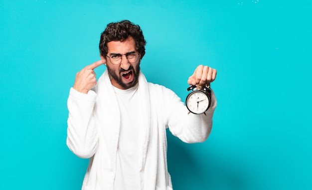 Joven loco barbudo vestido con albornoz y un reloj despertador