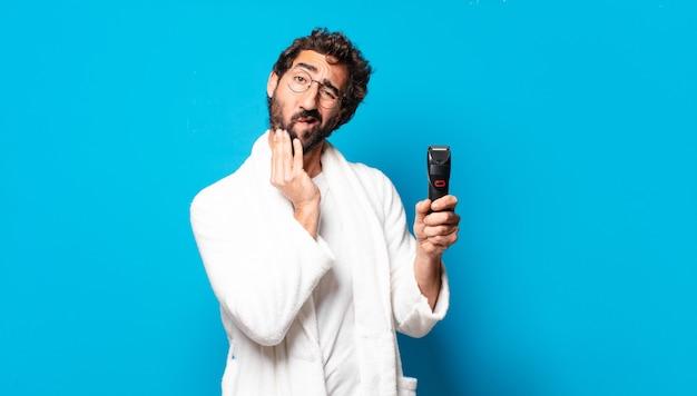 Joven loco barbudo vistiendo bata de baño concepto de afeitado