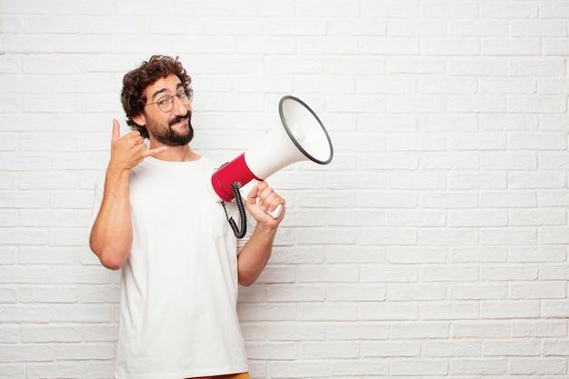 Joven loco con un megáfono contra la pared de ladrillo.