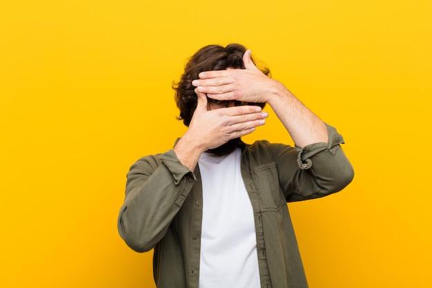 Joven loco cubriéndose la cara con ambas manos diciendo que no! rechazar fotos prohibir fotos pared amarilla