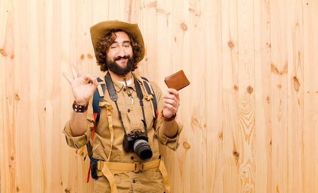 Joven loco explorador con sombrero de paja y mochila sobre fondo de madera