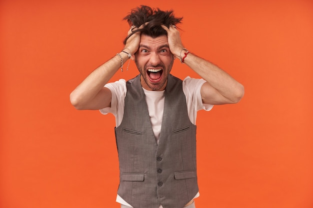 Joven loco loco con cerdas y cabello parado mantiene las manos en la cabeza gritando y mirando a la cámara