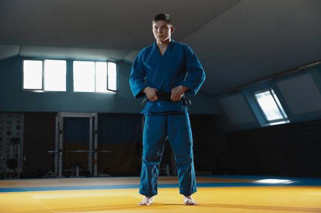 Joven luchador caucásico de judo en kimono azul con cinturón negro posando confiado en el gimnasio, fuerte y saludable.