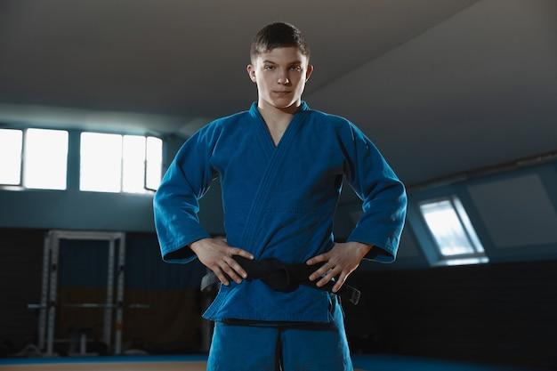 Joven luchador de judo en kimono posando cómodo en el gimnasio fuerte y saludable