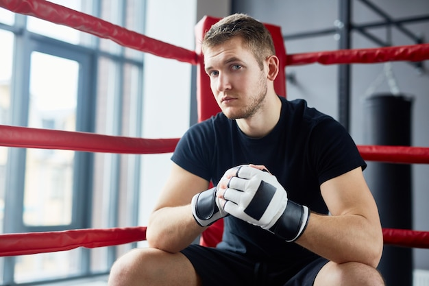 Joven luchador sentado en el ring de boxeo
