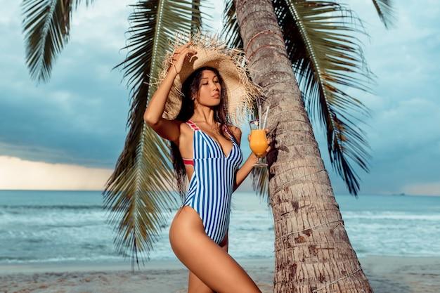 Una joven lujosa en bikini y sombrero de paja está de pie con un vaso de jugo de naranja debajo de una palmera en una playa tropical.