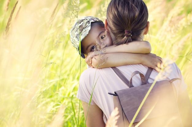 Una joven madre abraza fuertemente a su hijo en la hierba alta del verano.