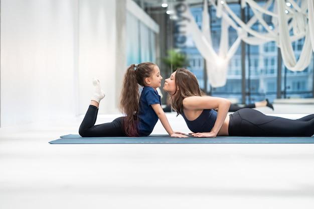 Joven madre adulta y pequeña hija juntas en aeróbicos