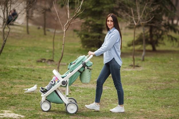Joven madre alegre caminando con su hijo en carriege