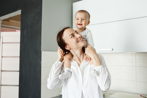 Joven madre alegre con su bebé sobre los hombros y riendo